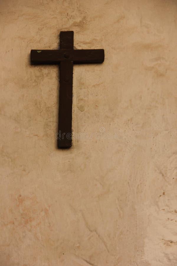 Uma cruz preta em uma parede cinzenta fotografia de stock