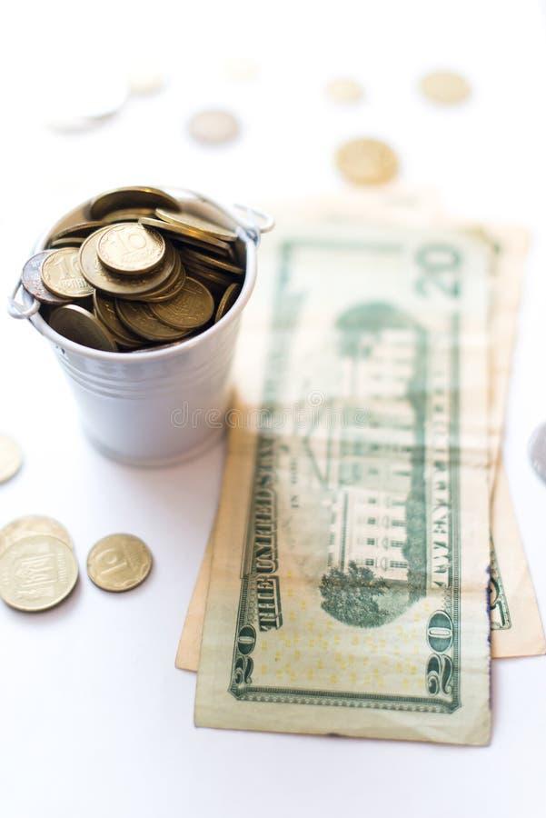 Uma cubeta com dólares das moedas de um centavo em um fundo branco foto de stock