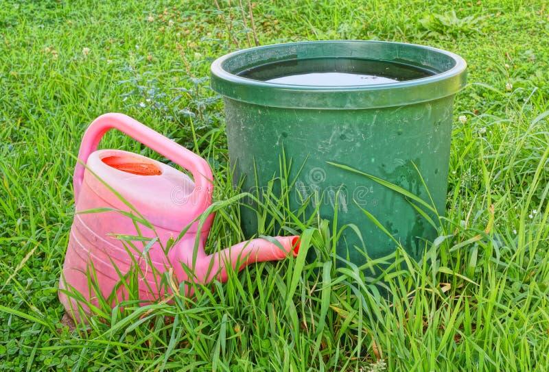 Uma cubeta da lata da água e molhar na grama imagens de stock royalty free