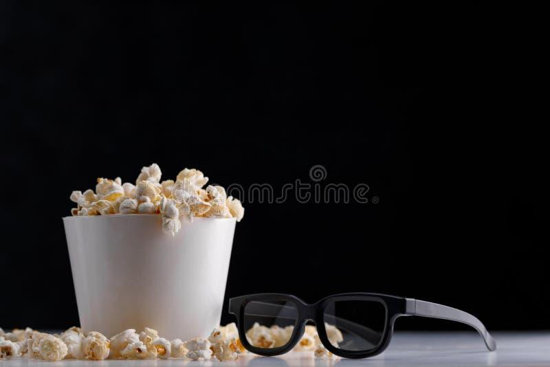 Uma cubeta da pipoca e dos 3 vidros de d em um fundo escuro Oscar Film Academy Concept imagens de stock royalty free
