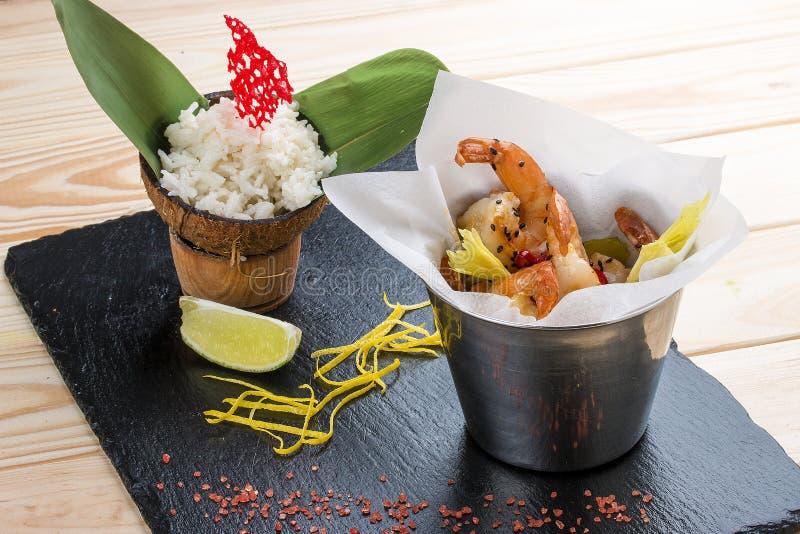 Uma cubeta do camarão no estilo asiático com arroz no leite de coco foto de stock