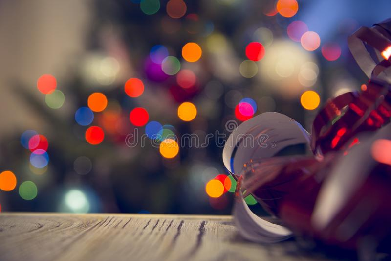 Uma curva metálica vermelha encaracolado em uma tabela de madeira contra a árvore de Natal decorada imagem de stock
