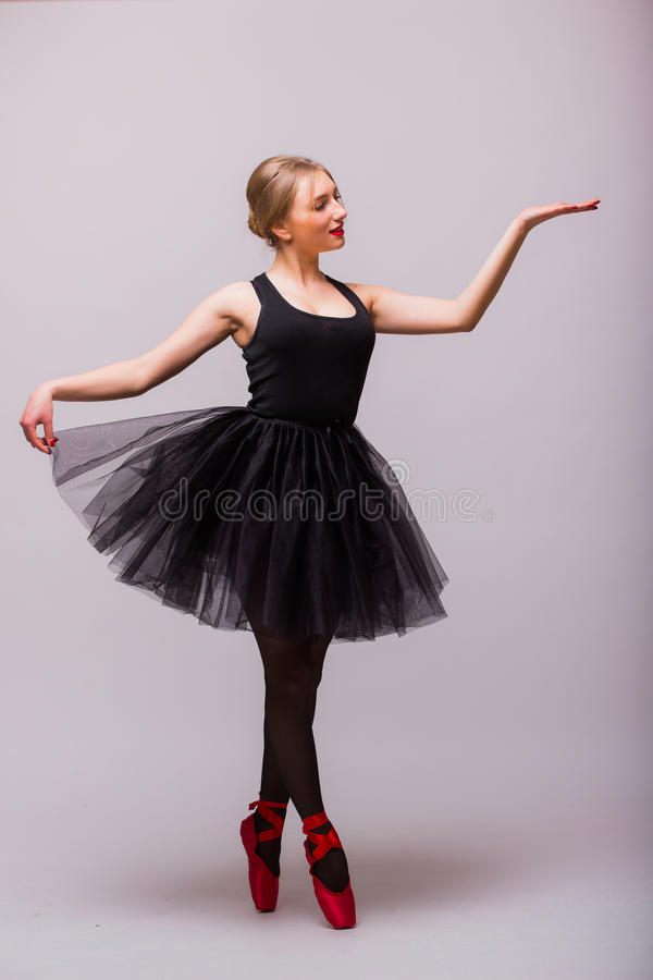 Uma dança caucasiano do dançarino de bailado da bailarina da jovem mulher com o tutu no estúdio da silhueta fotografia de stock