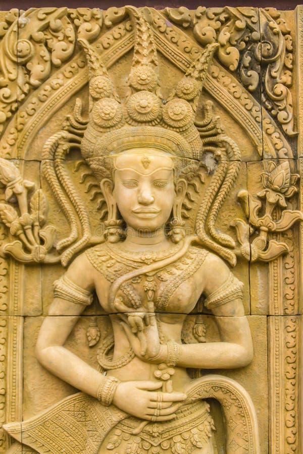 Uma dança de Apsara cinzelou no fundo da parede do arenito Apsara é um espírito fêmea das nuvens e das águas na cultura hindu Ele fotografia de stock royalty free