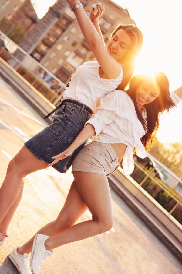 Uma dança despreocupada bonita de duas amigas tem o divertimento no estacionamento no fundo da cidade de nivelamento do por do so fotos de stock