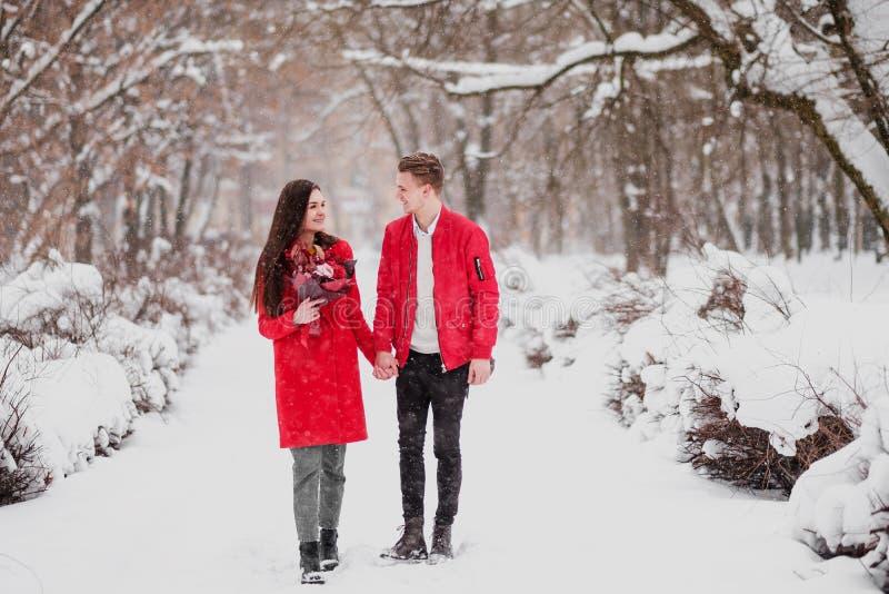 Uma data dos amantes com meu parque no inverno Um ramalhete de flores vermelhas, caminhada, abraço, beijo, riso em um ajuste româ foto de stock