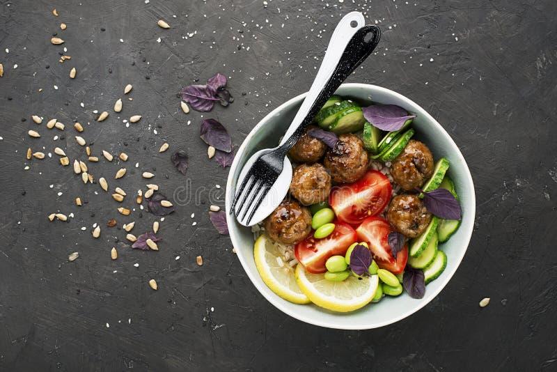 Uma dieta saudável, equilibrada, saudável Bolas de carne, tomates, arroz, pepinos, feijões da soja, espinafres, limão, bacia Vist fotografia de stock royalty free