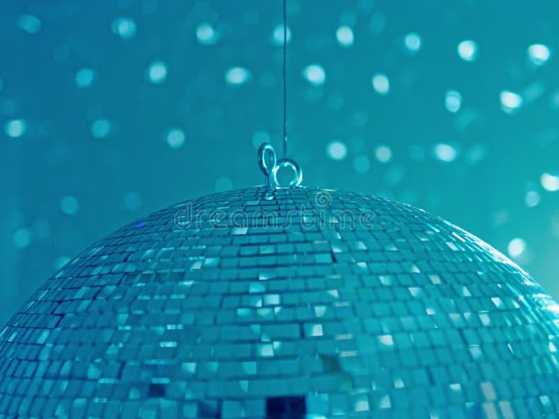 Uma disco-bola de suspensão e de giro enorme reflete flashes claros em uma parede brilhante e cria um humor relaxado foto de stock royalty free