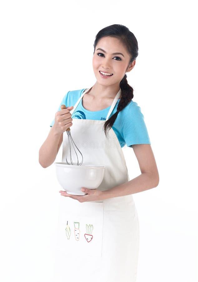 Uma dona de casa que agita ovos foto de stock