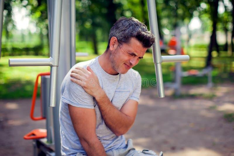 Uma dor do sentimento do homem em seu ombro durante o esporte e exercício em t fotos de stock