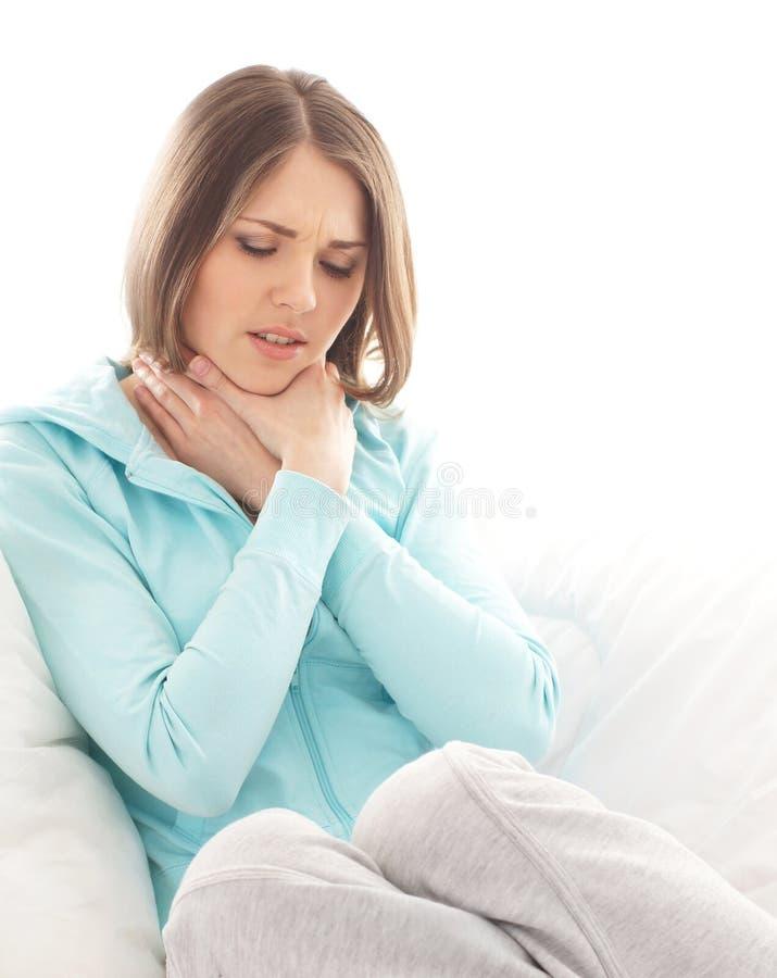 Uma dor moreno nova do sentimento da mulher em sua garganta imagens de stock royalty free