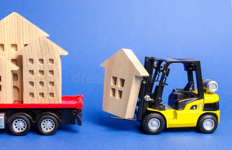 Uma empilhadeira amarela carrega uma figura de madeira de uma casa em um caminhão Conceito do transporte do transporte e de carga imagem de stock royalty free
