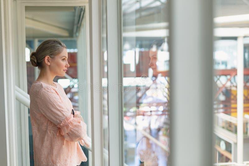 Uma empresária cuidadosa com braços cruzados na sala de conferências imagem de stock