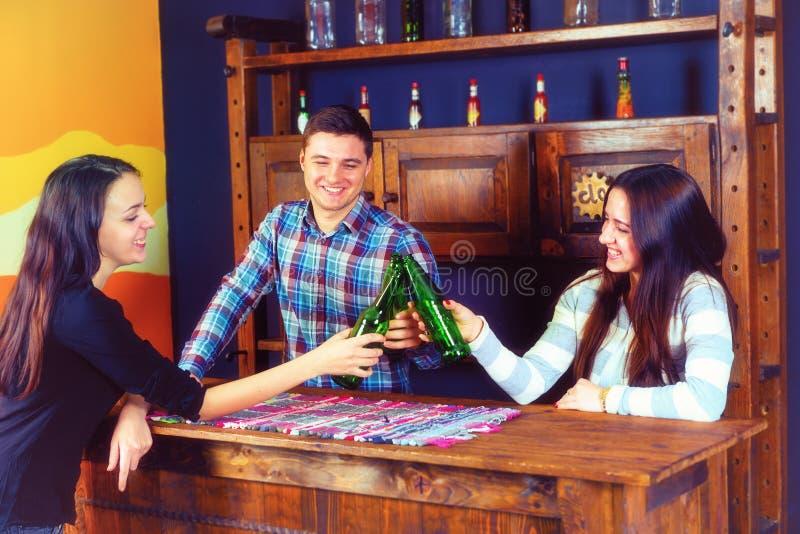 Uma empresa de garrafas felizes do tinido dos jovens da cerveja quando s foto de stock