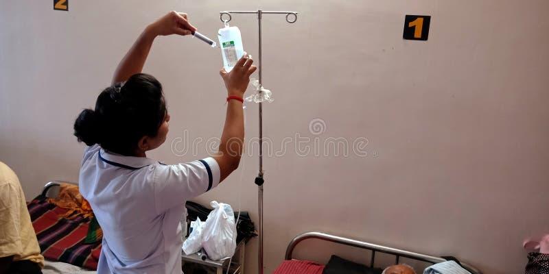 uma enfermeira indiana a injetar agulha no frasco durante o tratamento no dia aug 2019 fotos de stock