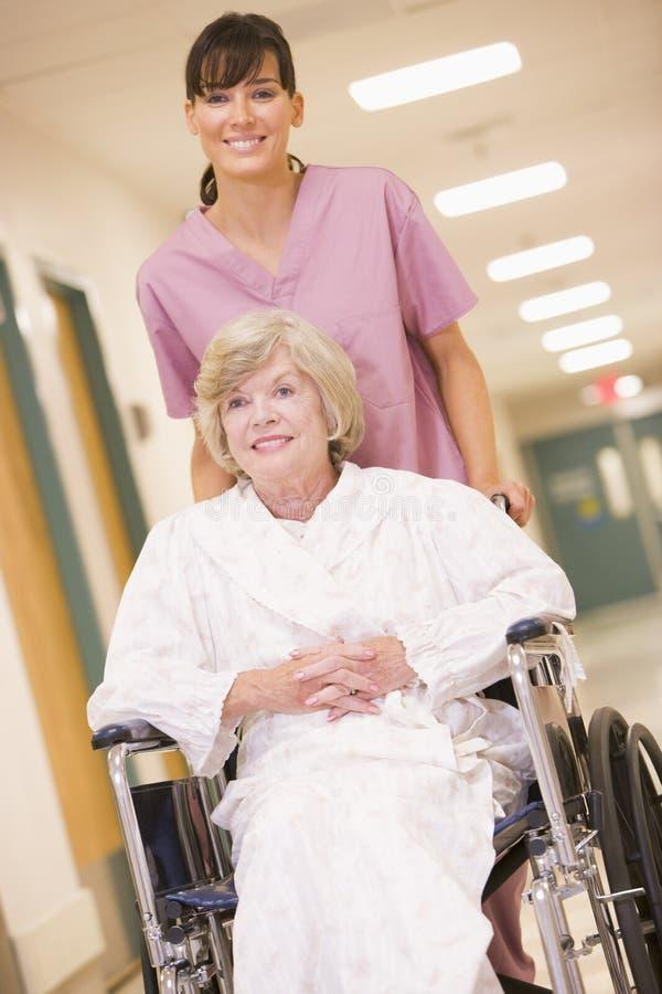 Uma enfermeira que empurra uma mulher sênior em uma cadeira de rodas imagem de stock