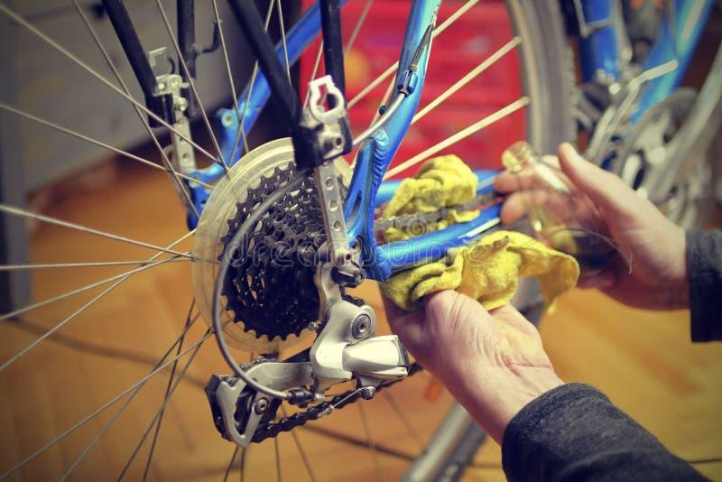 Uma engrenagem e uma corrente Lubrificação e reparação da movimentação da bicicleta Manutenção da bicicleta antes da equitação fotografia de stock