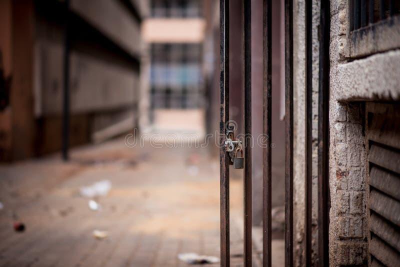 Uma entrada barrada metal com uma posição do cadeado aberta contra imagens de stock royalty free