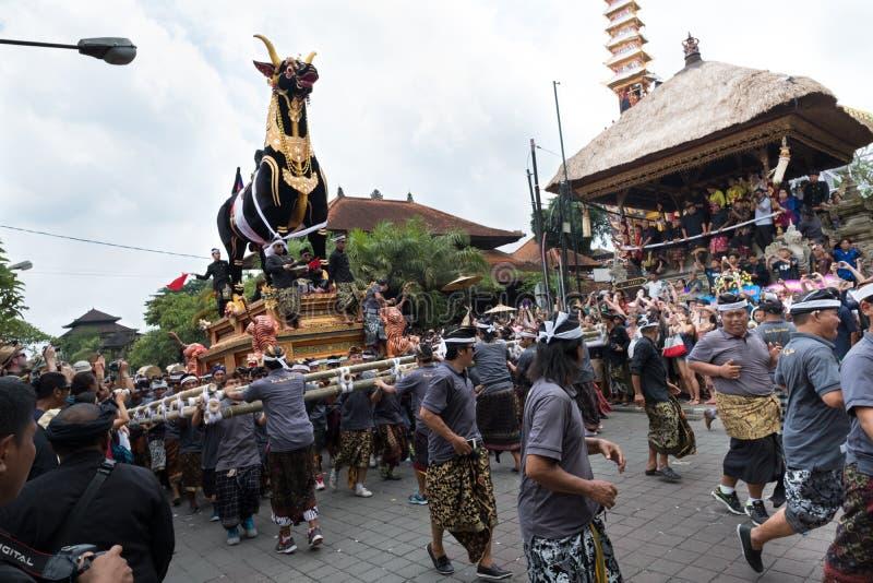 Uma equipe de homens do Balinese levanta o touro de Sarcopagus durante família real Ngaben cerimônia o 2 de março de 2018 imagens de stock royalty free