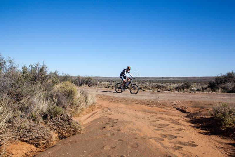 Uma equitação do ciclista em uma estrada de terra no Karoo seco do deserto fotografia de stock royalty free