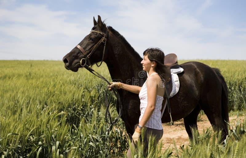 Uma equitação fêmea em um cavalo preto imagens de stock