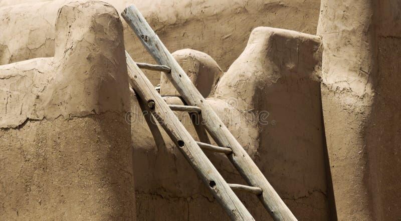 Uma escada do log inclina-se contra uma parede do estuque fotos de stock royalty free