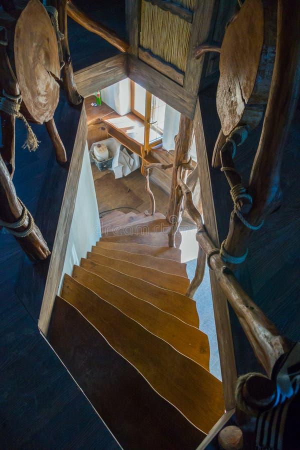 Uma escadaria de madeira íngreme no pavimento mais inferior à janela na casa com um interior interessante imagem de stock