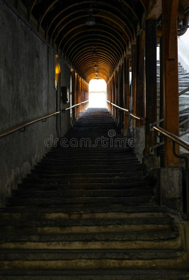 Uma escadaria de pedra velha longa coberta com um telhado de madeira em Thun foto de stock