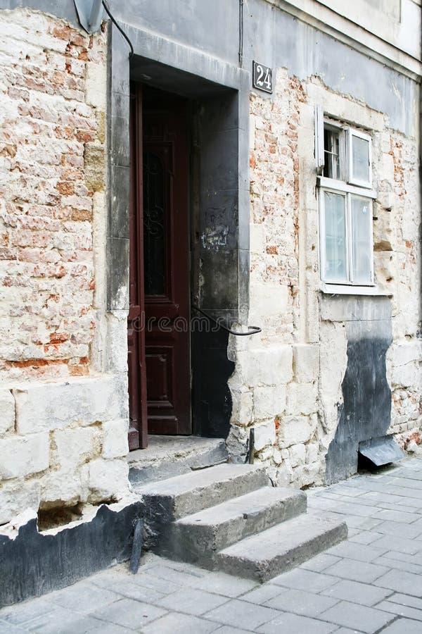 Uma escadaria e um estar aberto que conduzem a uma casa velha do tijolo Há uma janela ao lado da porta imagens de stock royalty free