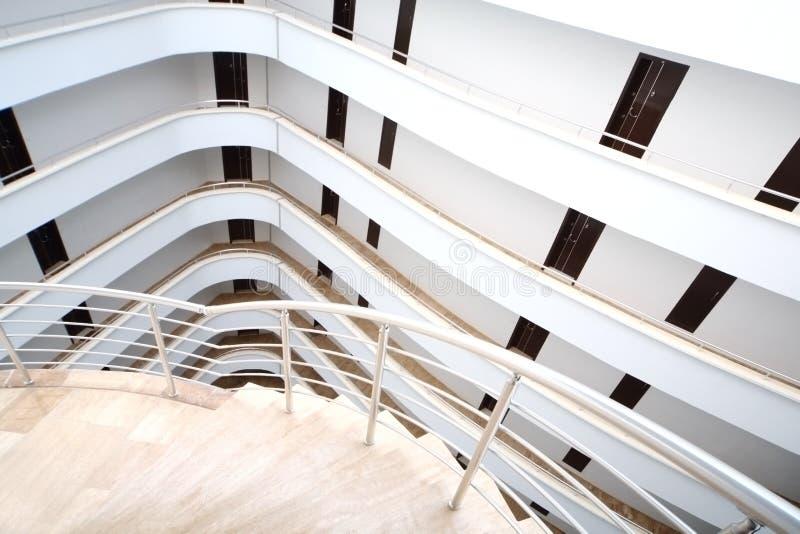 Uma escadaria espiral e uns balcões brancos foto de stock