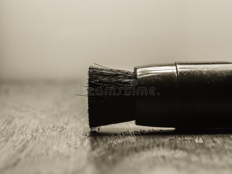 Uma escova de limpeza pequena que encontra-se em uma tabela de madeira fotos de stock royalty free
