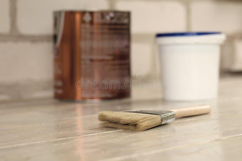 Uma escova de pintura é ao lado de uma cubeta plástica da pintura com uma lata azul da tampa e do metal em uma placa de madeira d fotos de stock royalty free