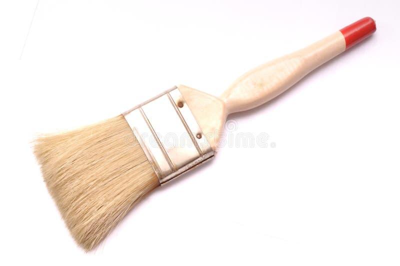 Uma escova de pintura do ` s do decorador com bege coloriu o punho fotografia de stock