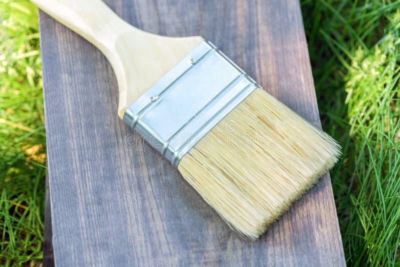 Uma escova de pintura larga encontra-se em uma placa de madeira na grama verde no close-up da rua Pinte a escova no backgroun de  fotografia de stock royalty free