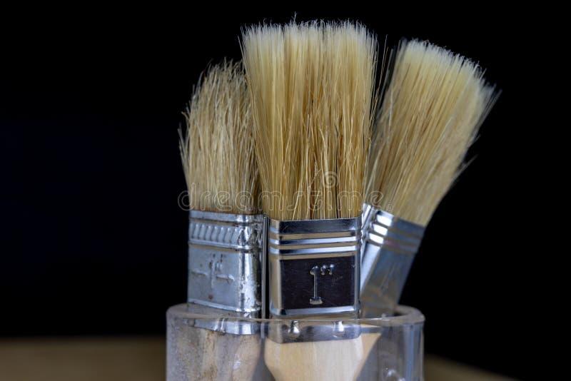 Uma escova para trabalhos domésticos simples e uma lata da pintura Accessor do reparo foto de stock royalty free