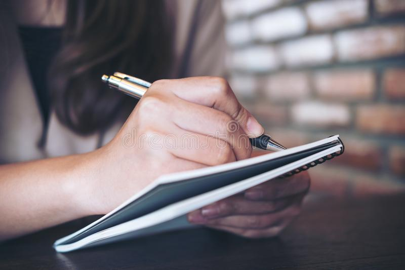 Uma escrita da mulher de negócio e uma nota da tomada no caderno no escritório foto de stock royalty free