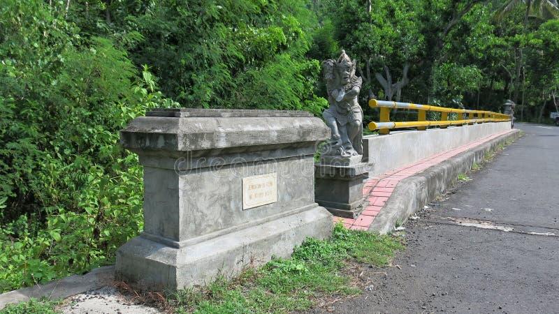 Uma escultura de pedra situada na extremidade da ponte é projetada proteger viajantes Estátua do protetor da mitologia do Balines fotografia de stock royalty free