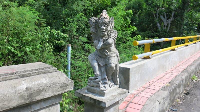 Uma escultura de pedra situada na extremidade da ponte é projetada proteger viajantes Estátua do protetor da mitologia do Balines foto de stock royalty free
