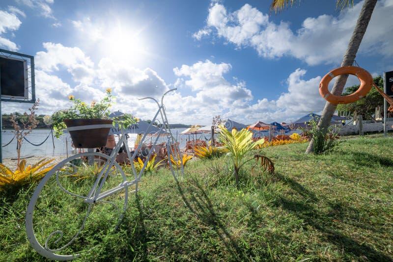 Uma escultura do bycicle em um jardim verde perto da costa com água tranquilo fotos de stock royalty free
