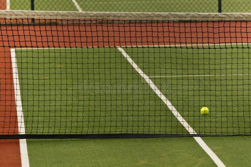 Uma esfera de tênis em uma corte foto de stock royalty free