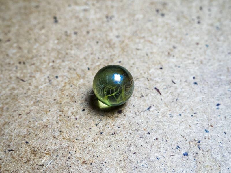 Uma esfera de vidro verde em uma superfície e em um cáustico de madeira imagens de stock royalty free