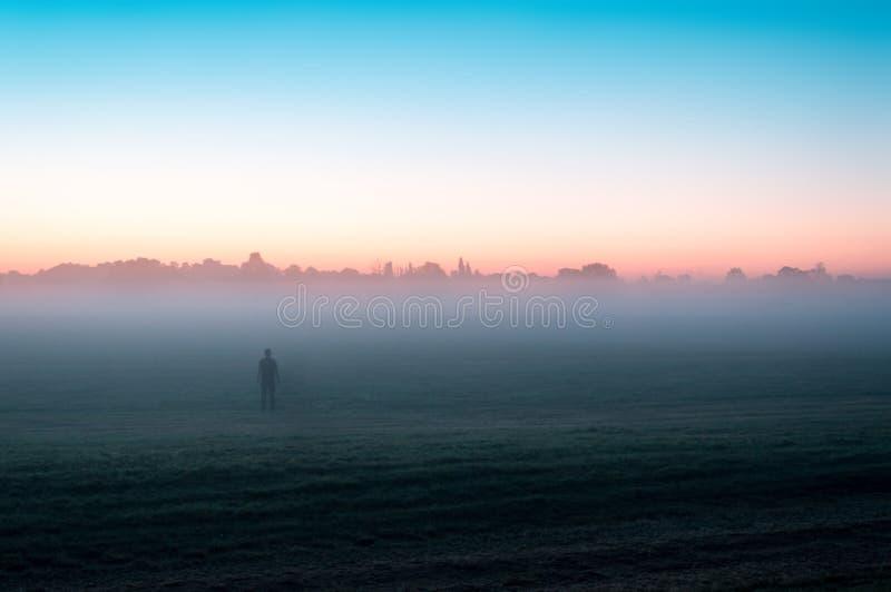Uma espectral solitário misterioso, figura posição em um campo imediatamente antes de imagem de stock