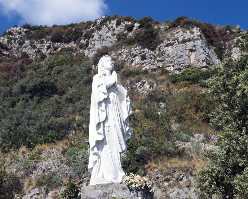 Uma estátua branca da Virgem Maria que reza ao longo da costa de Amalfi foto de stock