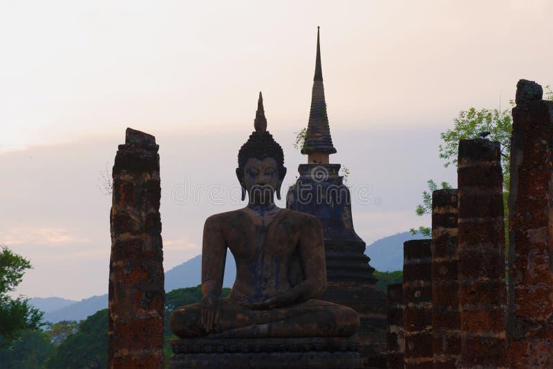 Uma estátua de uma Buda assentada nas ruínas do templo de Wat Chana Songkram no crepúsculo da noite Sukhothai, Tailândia fotos de stock royalty free