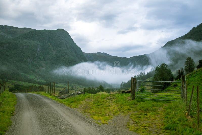 Uma estrada bonita do cascalho que conduz em um vale de Rosendal no parque nacional de Folgefonna, Noruega Paisagem de um dia nub foto de stock royalty free