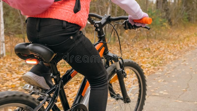 Uma estrada caucasiano da bicicleta dos passeios das crianças no parque do outono O ciclo alaranjado preto da equitação da menina imagem de stock