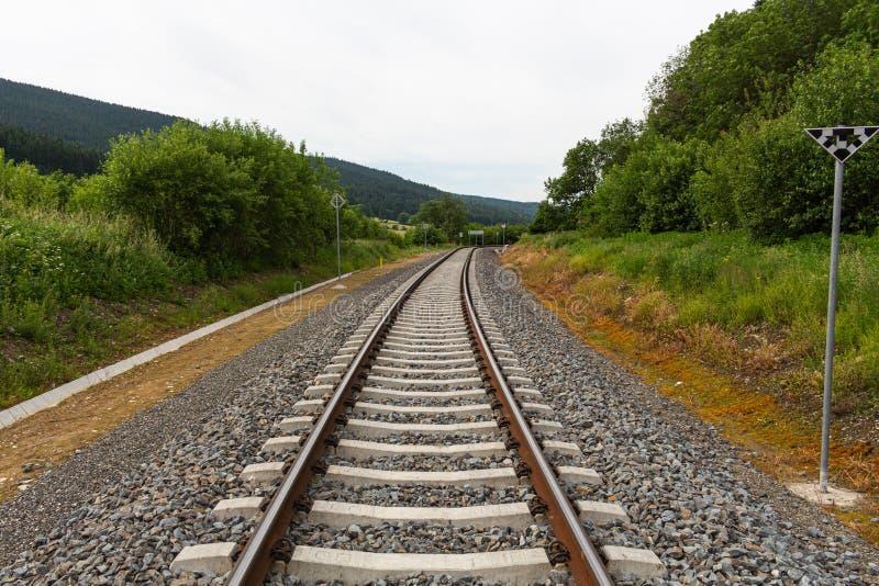 Uma estrada de ferro gerencie verticalmente através do campo do verde da mola O céu é brilhantemente azul com algumas nuvens bran imagens de stock royalty free