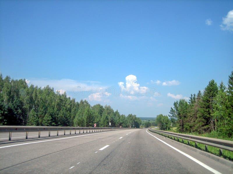 Uma estrada lisa, lisa corre para a frente através da floresta fotos de stock