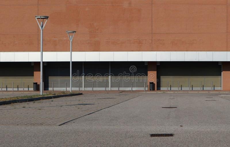 Uma estrada na frente de uma construção comercial marrom e branca com os obturadores da entrada fechado e os polos da rua Lâmpada imagem de stock royalty free