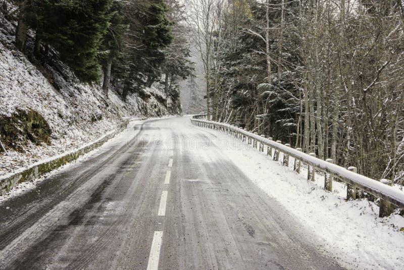 Uma estrada nevado e gelada nas montanhas imagem de stock